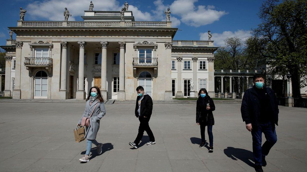 Les Polonais, soumis à un confinement moins sévère qu'en France, portent un masque lors de leurs déplacements, ici en avril au Parc Lazienki à Varsovie.