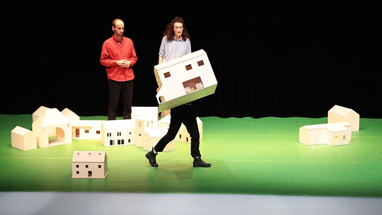 Le village en miniature est rebâti sous nos yeux par les comédiens.