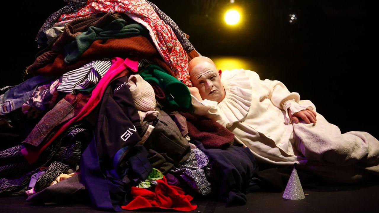 Gianluca Ballarè, le clown blanc, étendu sur un îlot de vêtements.