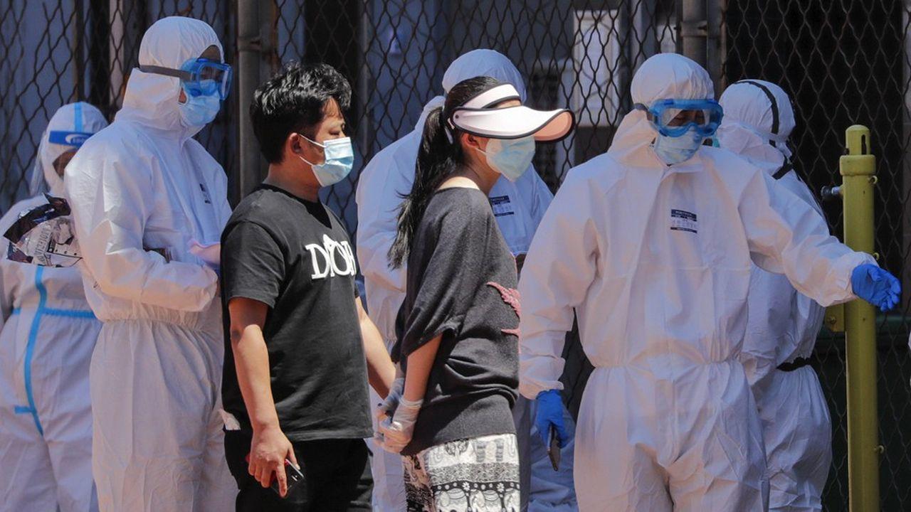 Des personnes vivant près du marché de gros de Xinfadi sont dirigées vers un stade de Pékin pour un test de dépistage du Covid-19