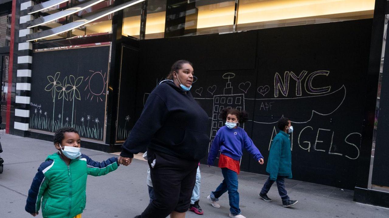 Une mère se promène avec ses enfants masqués à New York.