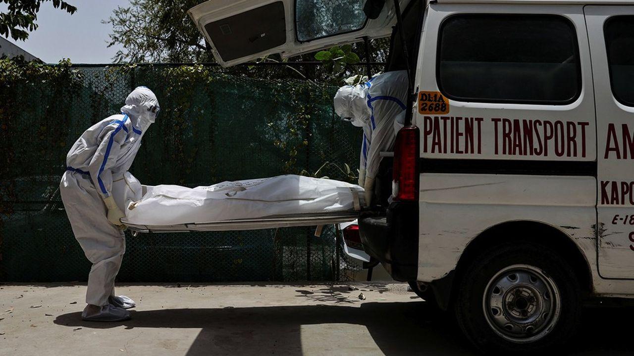 A New Delhi, fin mai, des travailleurs mortuaires transfèrent dans une ambulance le corps d'un Indien mort du SARS-CoV-2.
