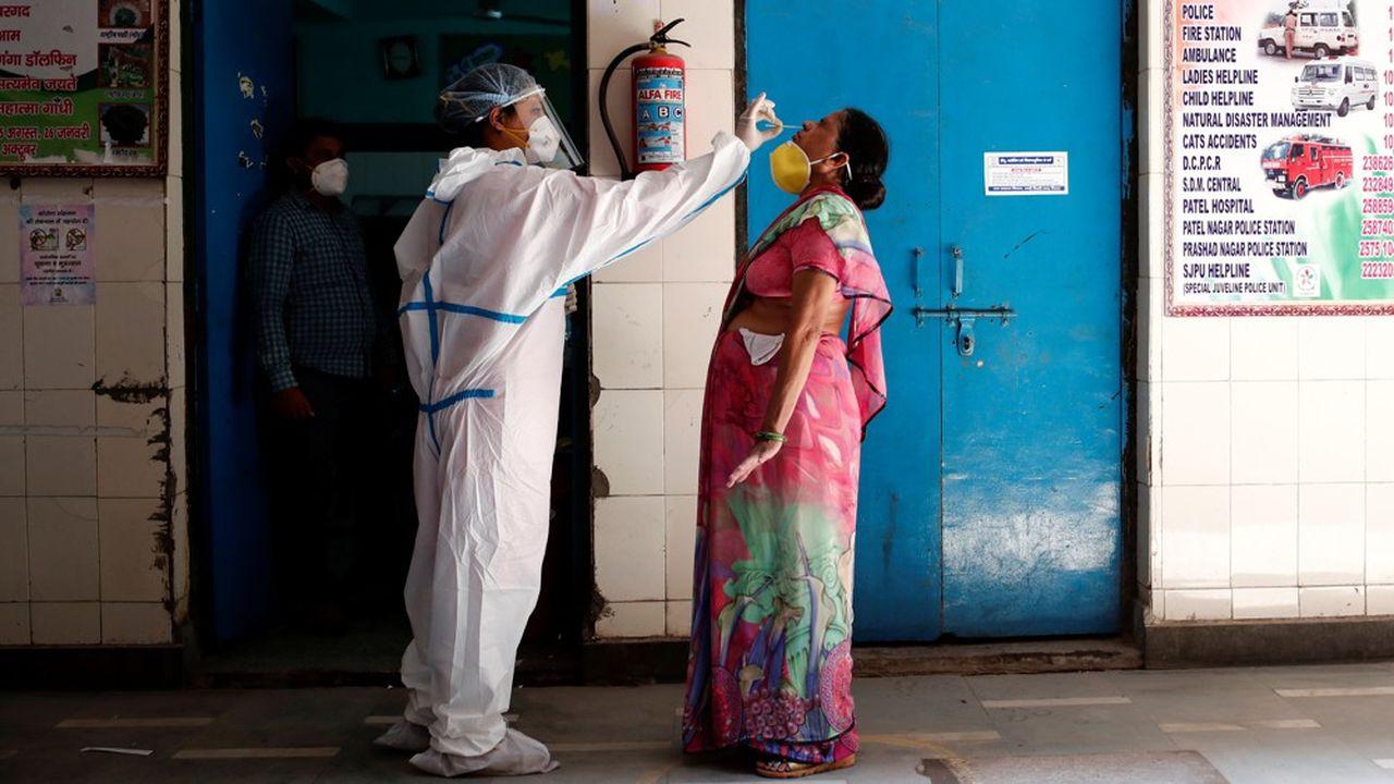 Un médecin effectue un test de Covid-19 sur une patiente dans une école transformée en centre de soins à New Delhi, capitale de l'Inde