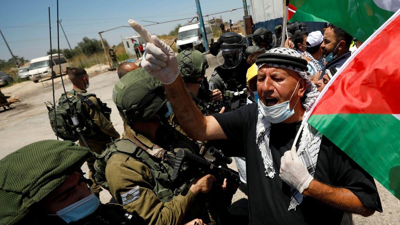 Un manifestant agitant le drapeau palestinien vitupère devant des soldats israéliens contre le projet d'annexion.