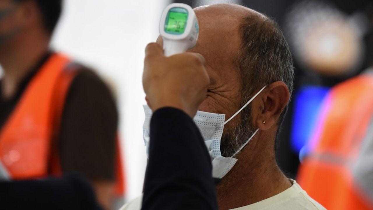 Une hôtesse vérifie la température d'un passager le jour de la réouverture de l'aéroport d'Orly à Paris le 26juin 2020. (Photo by ERIC PIERMONT/AFP)
