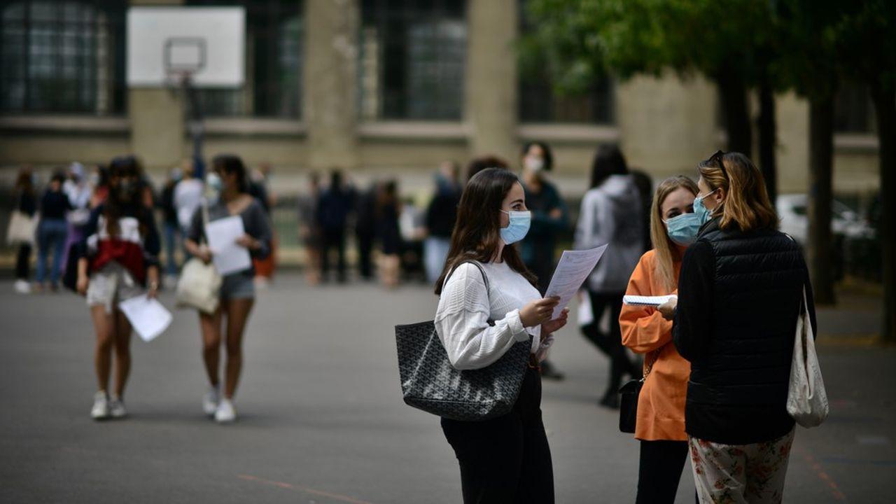 Dans certains établissements, comme ci-dessus au lycée Lafontaine à Paris (16e), des candidats au baccalauréat ont été invités, par petits groupes et dotés d'un masque, à récupérer les moyennes des notes obtenues à l'examen.