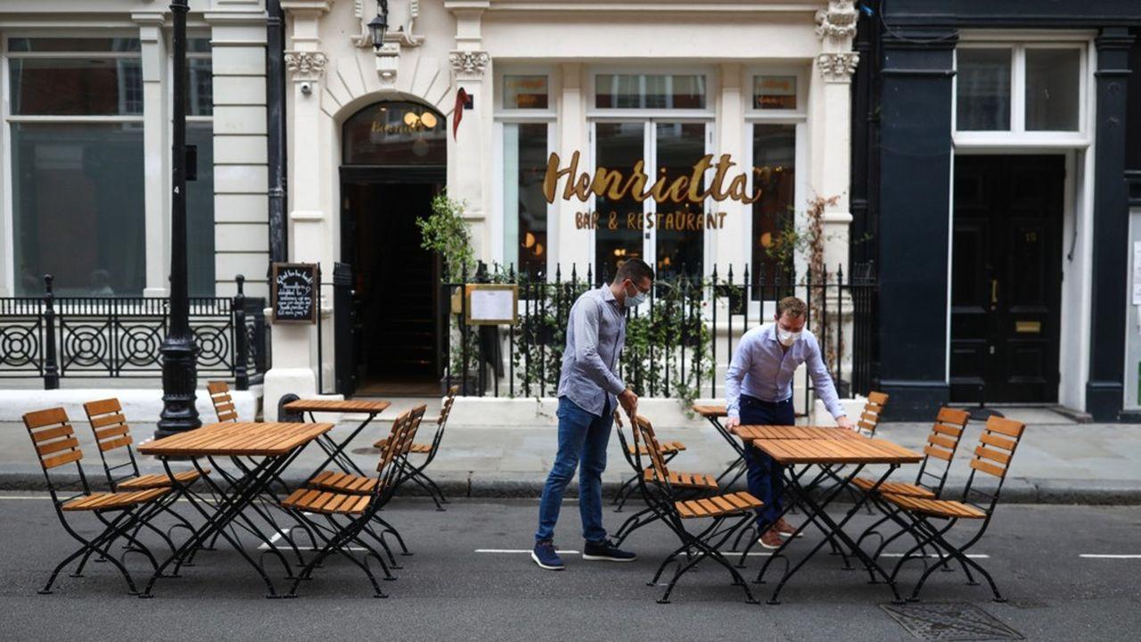 Des employés installent la terrasse du bar restaurant Henrietta, dans le quartier londonien de Covent Garden, samedi 4juillet, après 3 mois et demi de fermeture à cause du virus.