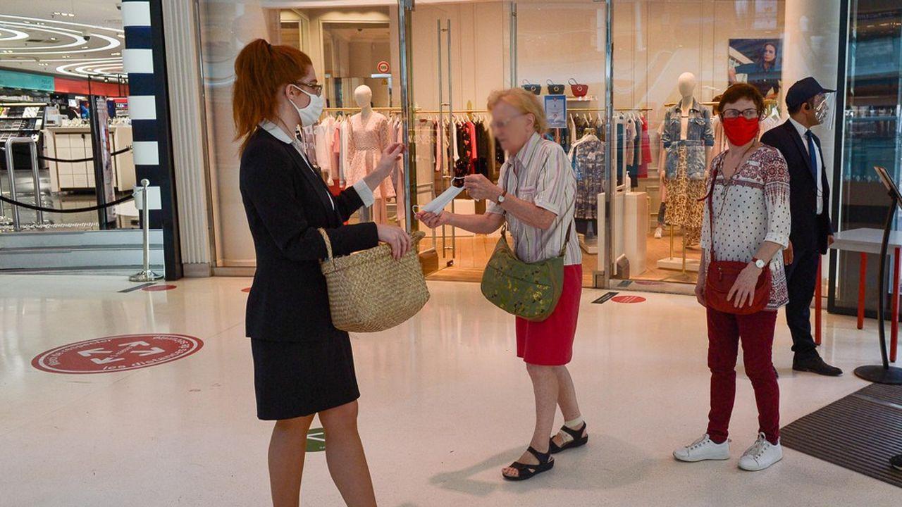 Le conseil scientifique alerte sur le relâchement des mesures barrières face au Covid-19 (ci-dessus une distribution de masques à l'entrée d'un centre commercial).