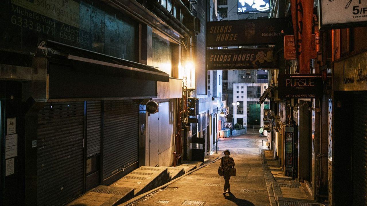 Hong Kong (photo: le quartier de Lan Kwai Fong) a décidé de fermer ses bars, ses salons de coiffures et autres échoppes pour se protéger du virus.
