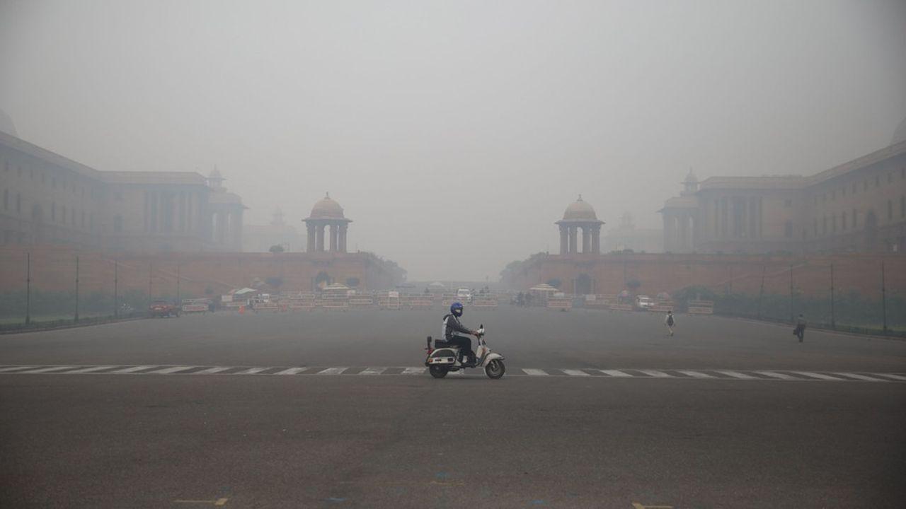 Un homme à scooter traverse une avenue de Delhi dans un brouillard de pollution.