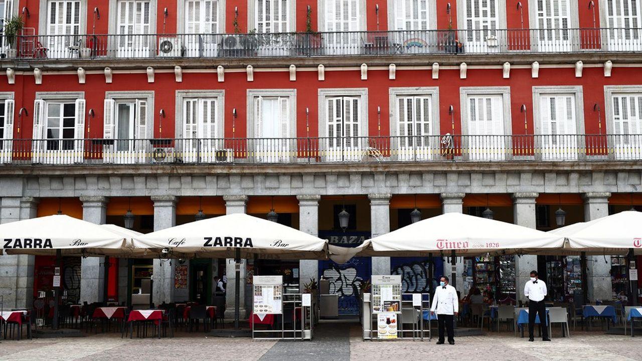 Des serveurs portant des masques chirurgicaux attendent la clientèle à Madrid, en Espagne, le 28juillet 2020.
