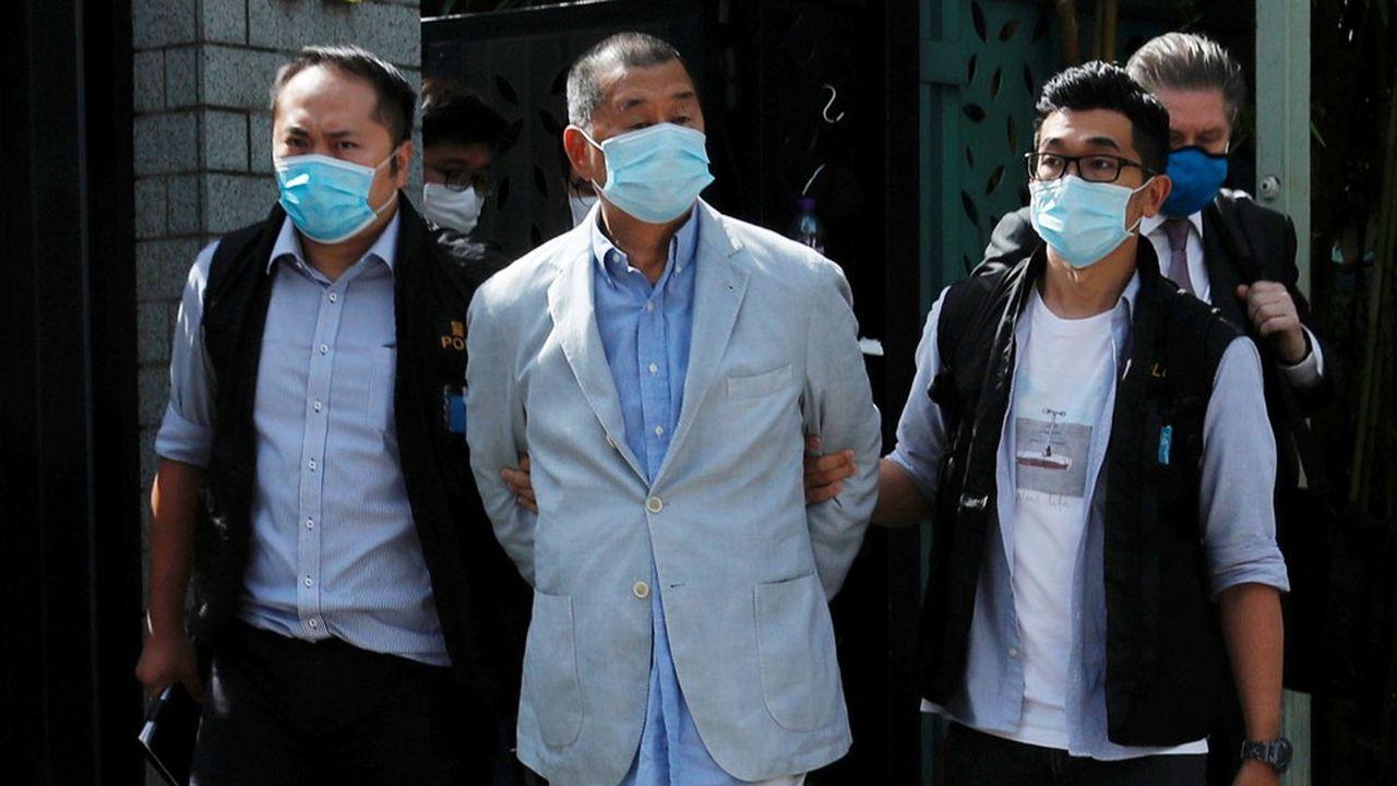 Le magnat de la presse et pro-démocratie Jimmy Lai Chee-ying est sorti de chez lui menotté, après son interpellation par la police ce lundi.