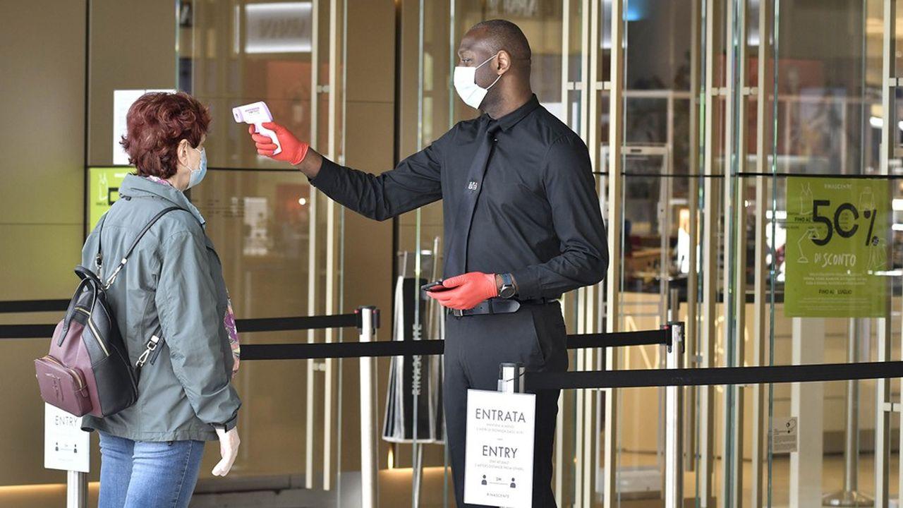 Prise de température d'un client à l'entrée d'un magasin, dans le centre de Turin.