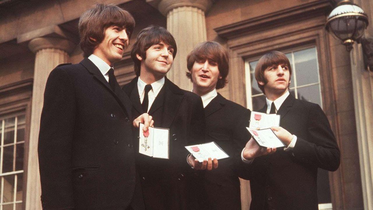 Les membres des Beatles, George Harrison, Paul McCartney, John Lennon et Ringo Starr, sur le parvis de Buckingham Palace après avoir été décorés de l'Ordre de l'Empire britannique, le 26octobre 1965.