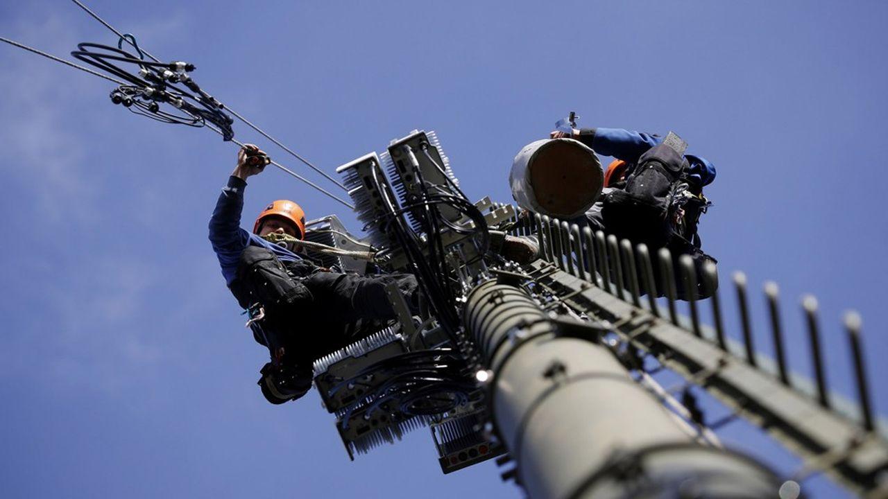 Des techniciens sur une antenne 5G en Suisse.