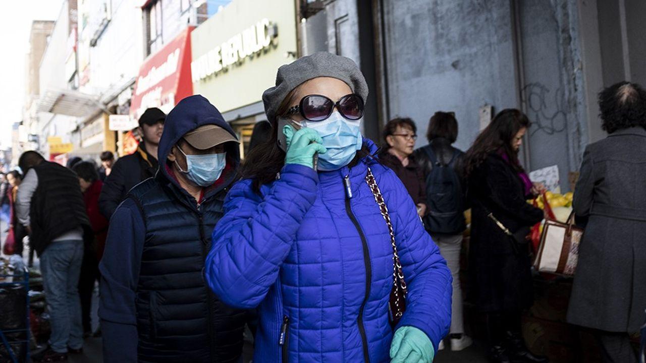 Des New-Yorkais, dans le populaire quartier du Queens, portent des masques pour se protéger du coronavirus.