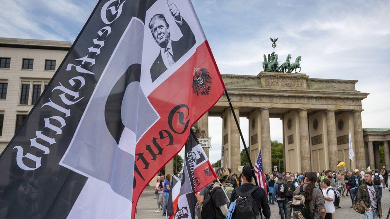Lors d'une manifestation d'extrême droite à Berlin, le 29août, un manifestant porte un drapeau du Reich avec l'effigie du président Trump.