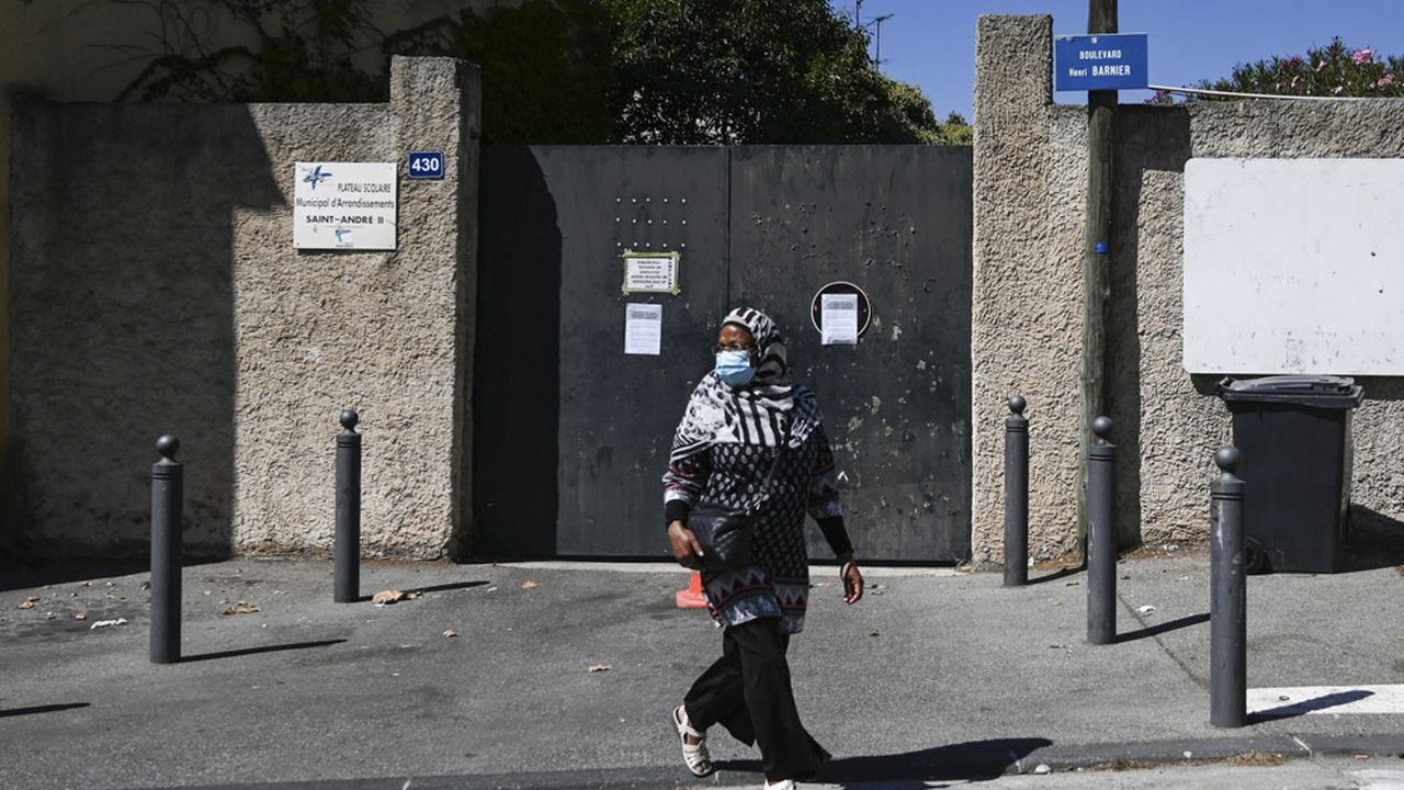 A woman walks in front of the entrance of the primary school Saint-Andre Condorcet closed due to a case Covid-19, in the southern French port city of Marseille on September 4, 2020. - France's education minister said today that 22 schools have had to shut on French territory due to the coronavirus since pupils returned to school this week, emphasising that over half of these were in the Indian Ocean island of La Reunion. (Photo by Christophe SIMON / AFP)