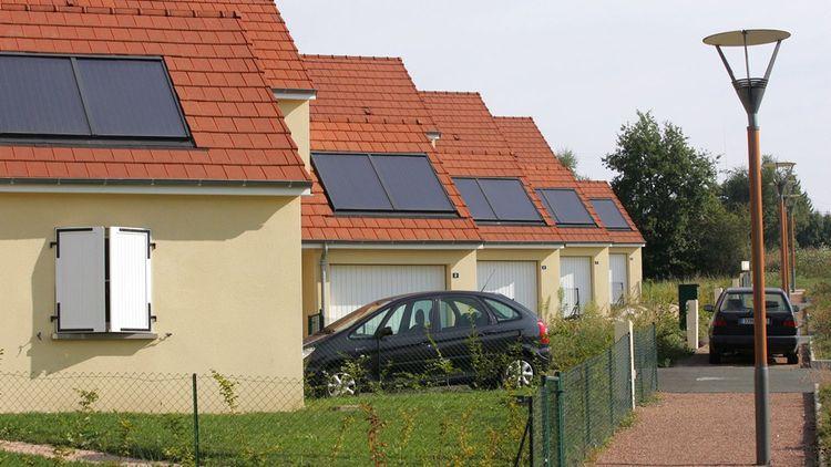 Panneaux solaires thermiques pour le chauffage et l'eau chaude sanitaire sur des pavillons HLM de l'Opac de Commentry en région Auvergne-Rhône-Alpes.