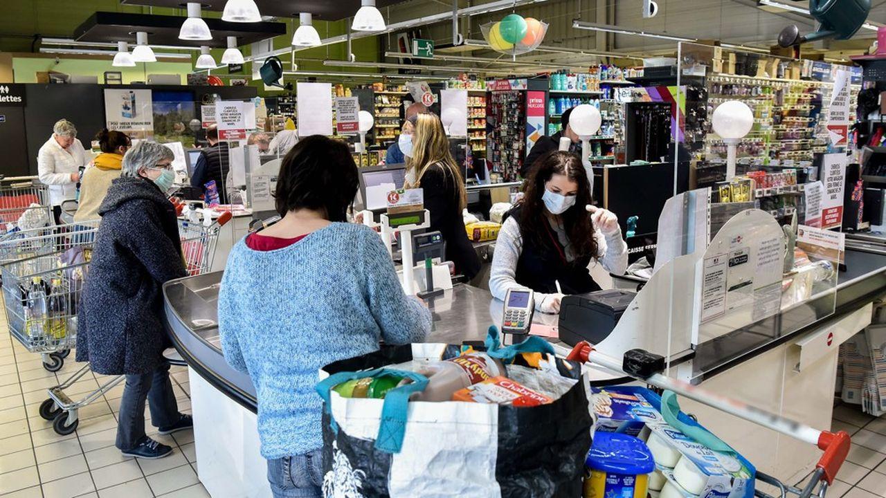 Des personnes font leurs courses achat au supermarche Intermarche pendant le confinement du a l 'epidemie de COVID 19. Les vendeuses sont masquees, et protegees par des vitres et du plexiglas . Le personnel masque rempli et reaprovisionne les rayons