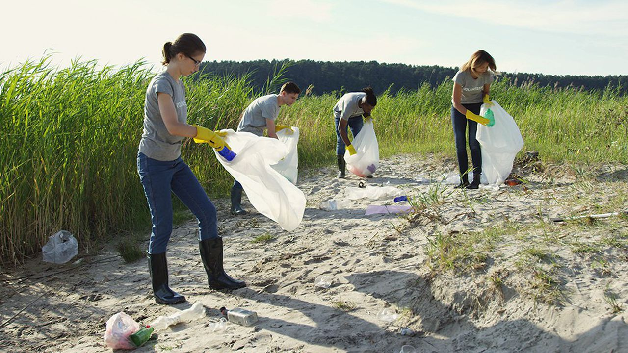 Group of young volunteers helping to keep nature clean and picking up the garbage from a sandy shore