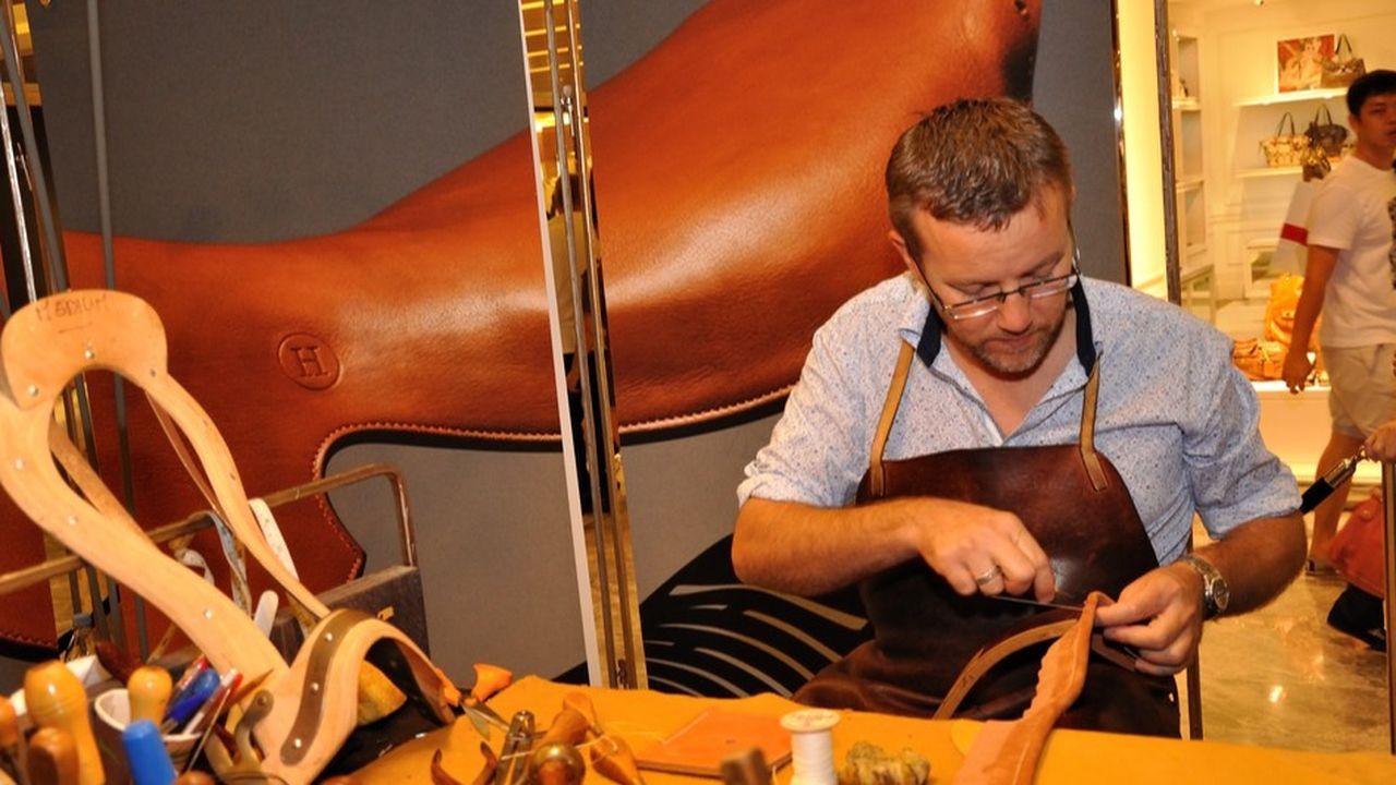 Tous les groupes familiaux, Michelin, Mulliez ou Hermès, ne raconteront pas la même histoire. Ici un artisan de la maison Hermès réalise une selle.