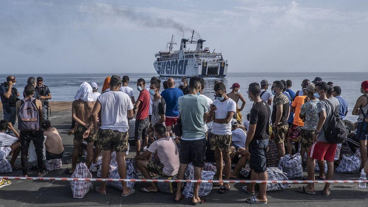 Des Tunisiens attendent un ferry qui va les reconduire en Sicile, sous escorte policière après avoir touché le sol italien à Lampedusa.