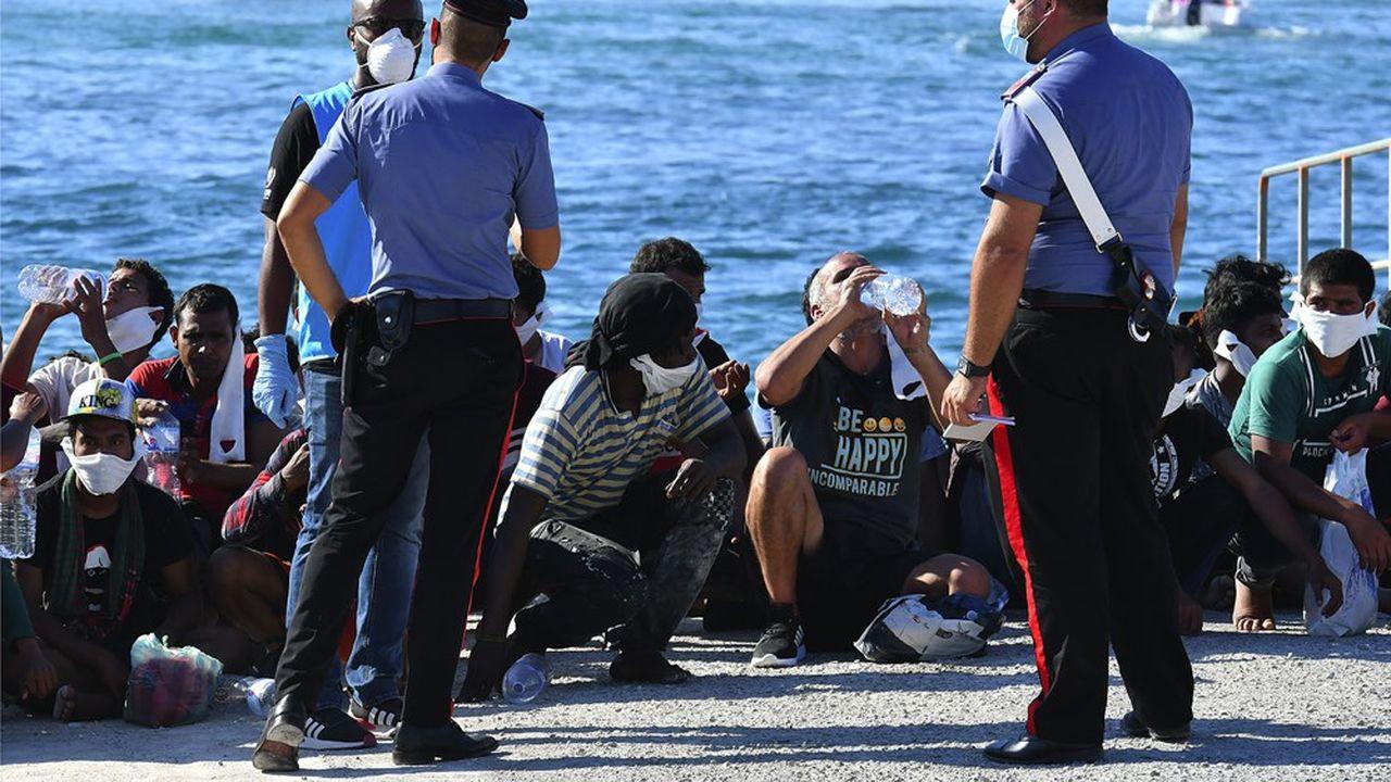 Des migrants secourus par les garde-côtes italiens débarquent sur l'île de Lampedusa le 29juillet 2020