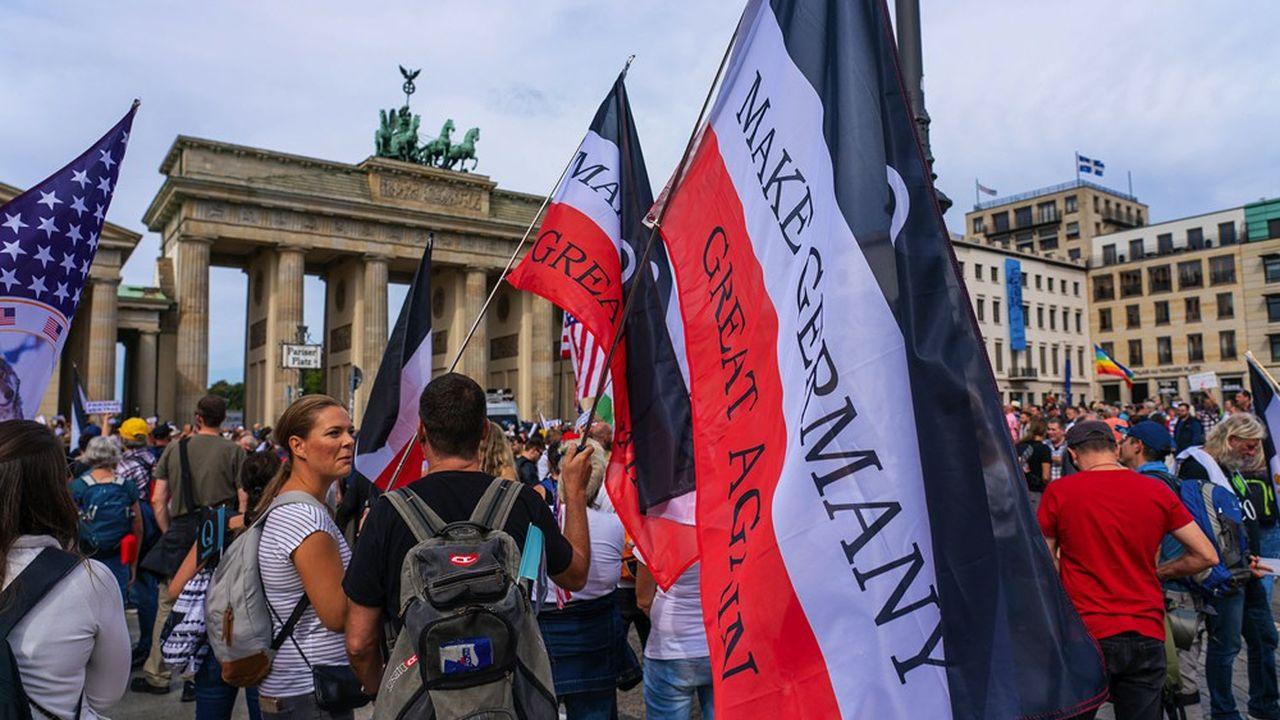 Le 29août, à Berlin, devant la porte de Brandebourg, des adeptes des théories du complot et opposés au port du masque, brandissent des drapeaux du mouvement QAnon avec le slogan «rendre sa grandeur à l'Allemagne» dans une allusion à Donald Trump.