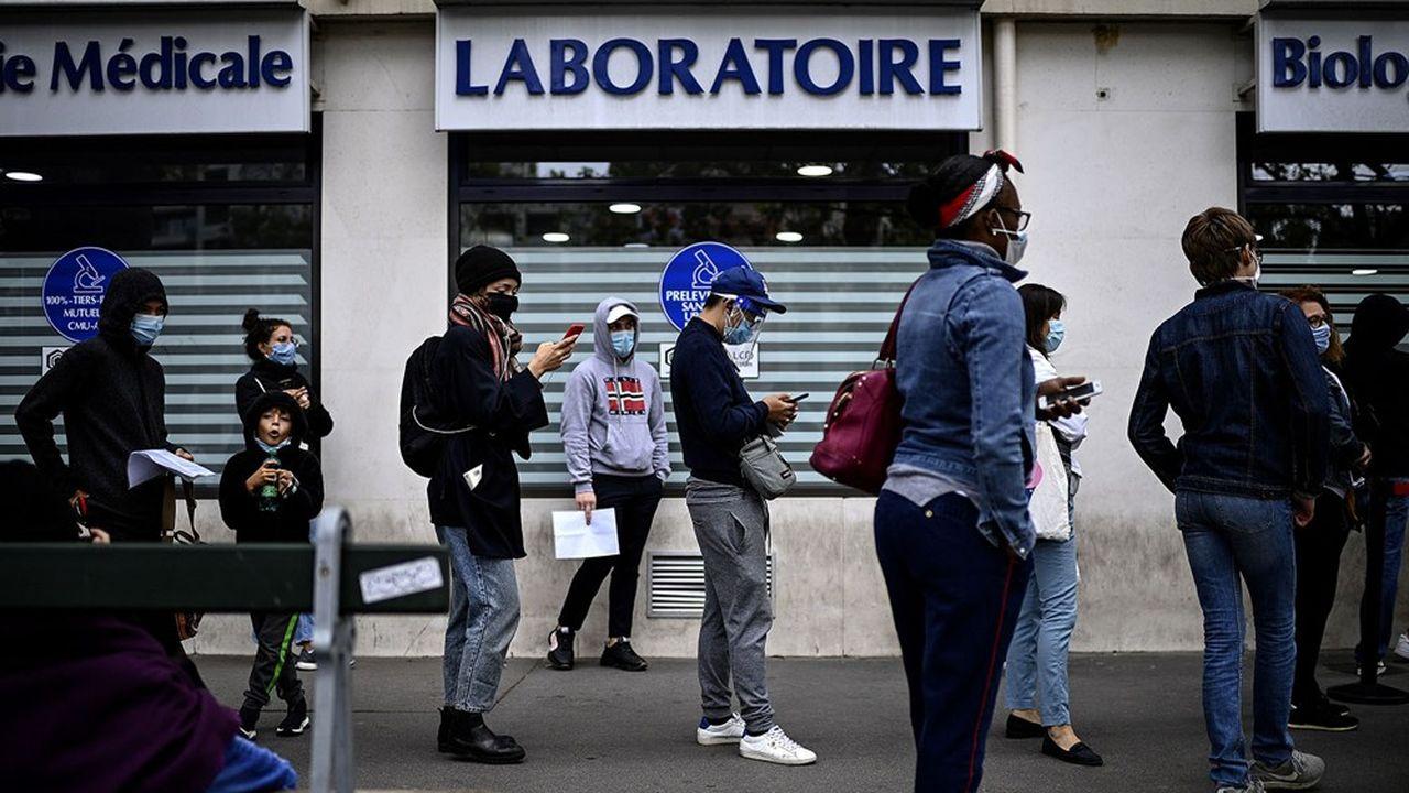 Des personnes font la queue devant un laboratoire parisien pour se faire dépister du Covid-19.