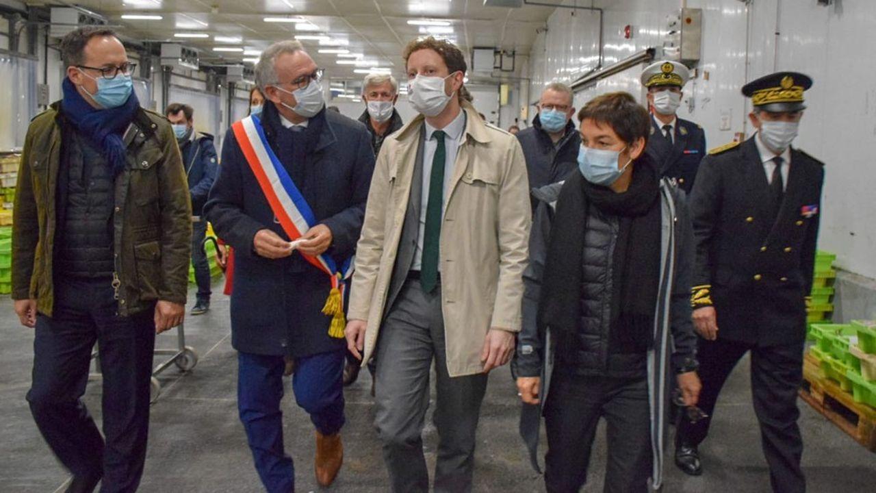 Annick Girardin, ministre de la Mer et Clément Beaune, secrétaire d'Etat aux Affaires européennes discutent dans la halle à marée avec le maire de Port-en Bessin.