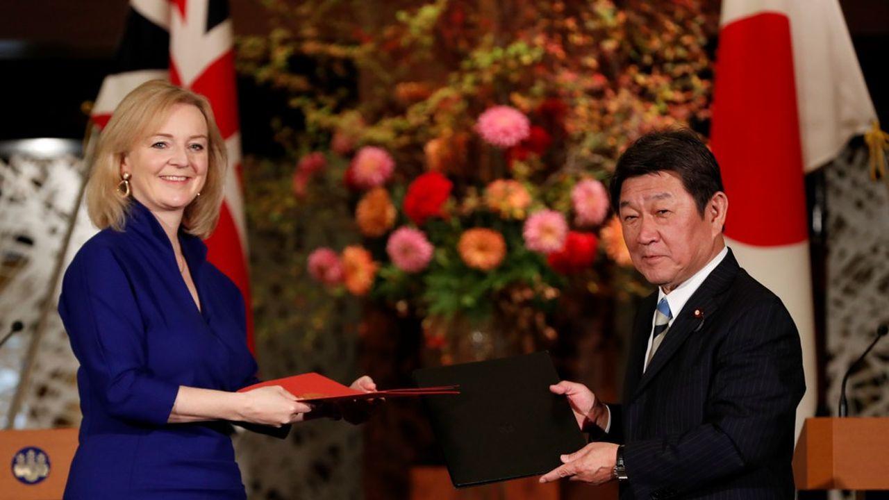 La ministre britannique du Commerce international Elizabeth Truss et le ministre japonais des Affaires étrangères Toshimitsu Motegi présentent à la presse les documents contenant l'accord de libre-échange entre les deux pays.