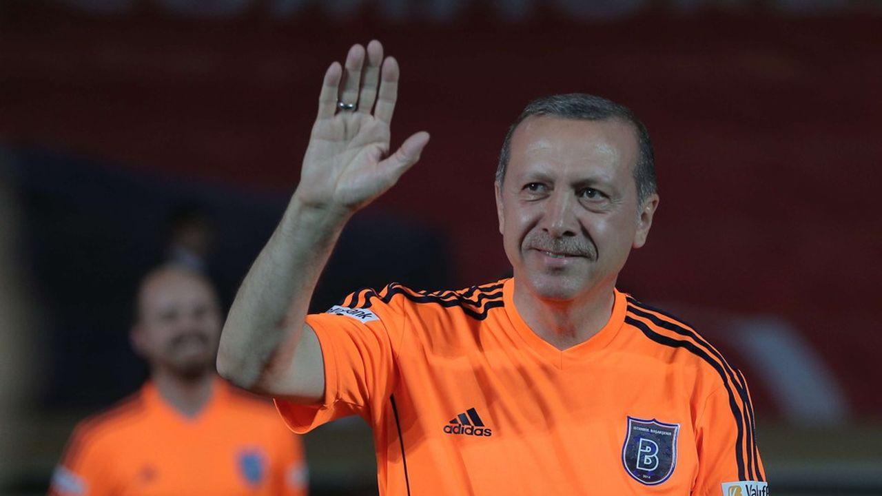 En juillet2014, le Premier ministre turc et candidat à la présidence Recep Tayyip Erdogan salue les supporters du Basaksehir -Istanbul avant de prendre part à un match de football exhibition, après la cérémonie d'ouverture d'un nouveau stade portant le nom du sélectionneur turc Fatih Terim, à Istanbul.