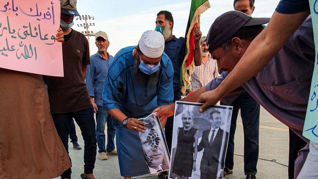 Des manifestants brûlent des images falsifiées du général Khalifa Haftar et d'Emmanuel Macron, souvent accusé d'avoir soutenu la rébellion de l'est de la Libye, lors d'une protestation le 25octobre à Tripoli.