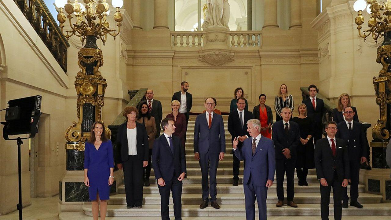 Alexander De Croo (premier rang) et les membres, dont quatre « héritiers », du nouveau gouvernement fédéral posent avec le roi Philippe (premier rang au centre) au Palais royal.