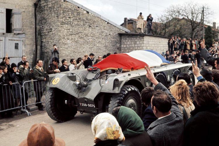 le cercueil du général Charles de Gaulle recouvert du drapeau tricolore, passe sur un véhicule blindé, le 12novembre 1970, dans le village de Colombey-Les Deux-Eglises, au milieu d'une foule qui lui rend hommage.