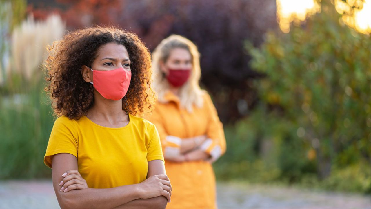 Friends wearing protective face mask on the street and protest silently during COVID-19 pandemic. Second wave of coronavirus