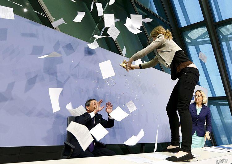 Le 15 avril 2015, en conférence de presse, Mario Draghi est aspergé de confettis par une militante dénonçant la dictature de la BCE au moment de la crise grecque.