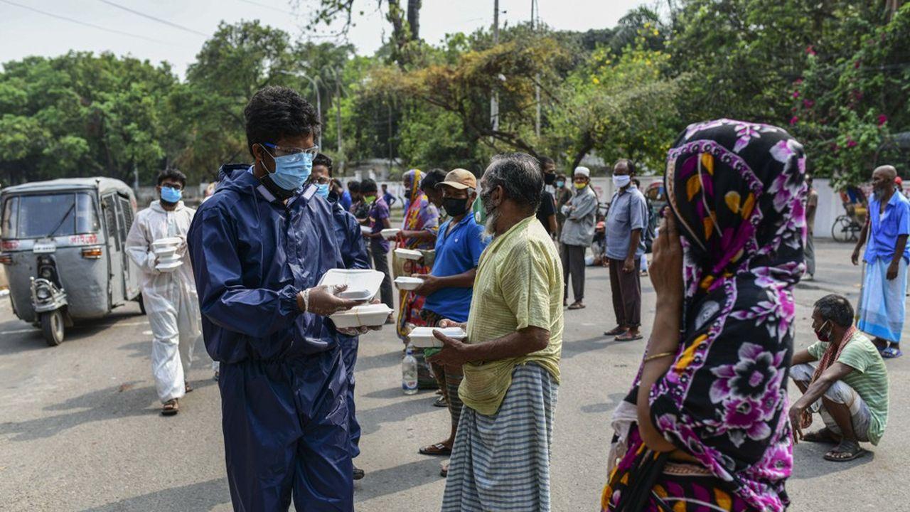 A Dhaka, auBangladesh, des volontaires distribuent de la nourriture à des personnes sans abris, le 20avril 2020.