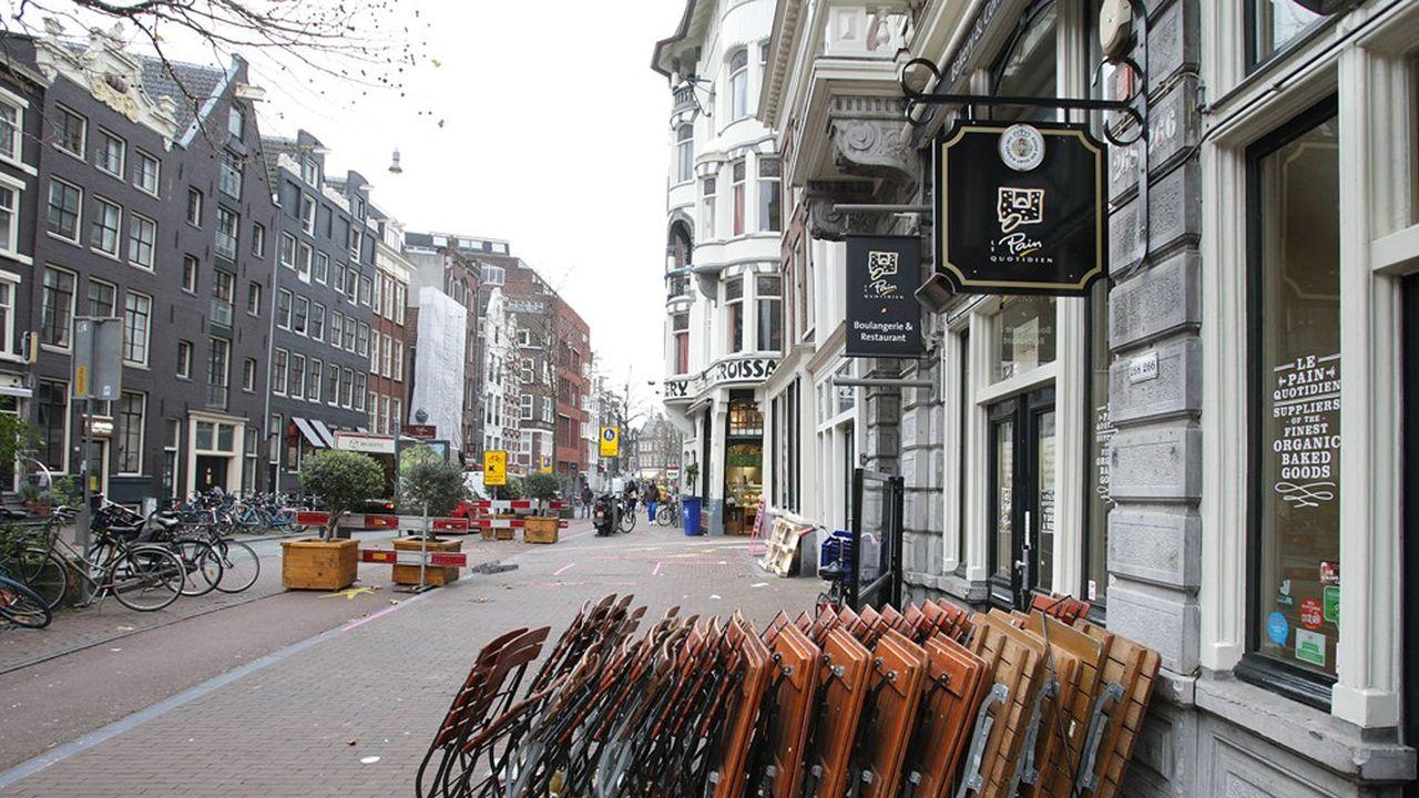 Des tables et des chaises attendent les clients devant les bars et les restaurants dans une rue du centre d'Amsterdam.