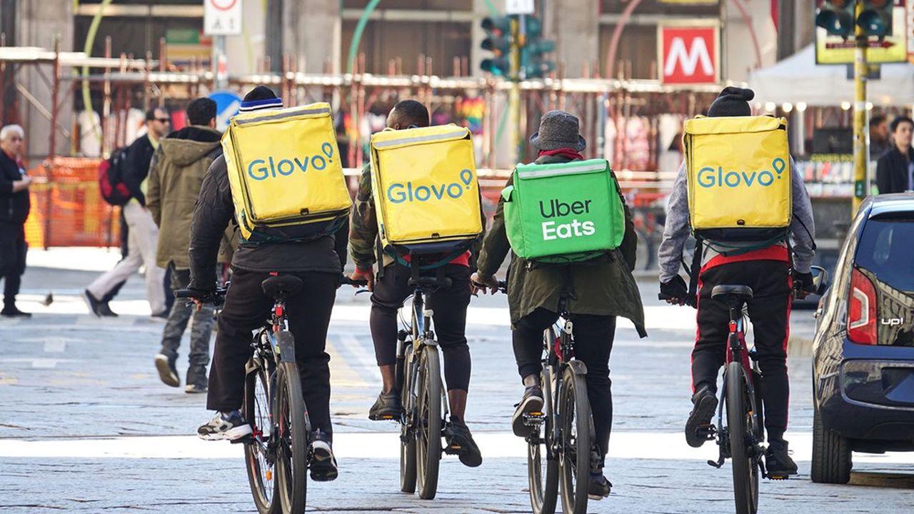 Des livreurs à vélo dans les rues de Milan.