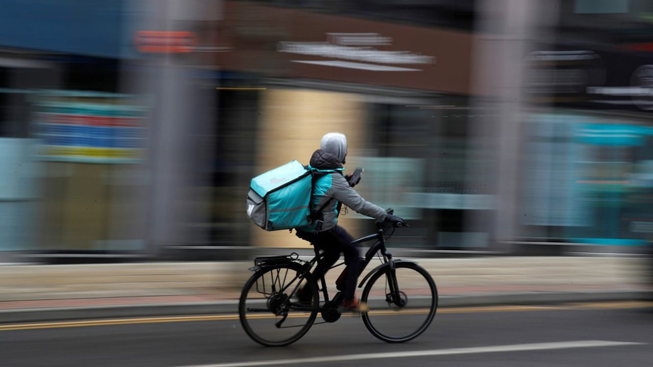A deliveroo delivery driver cycles through the centre of Manchester, Britain, March 8, 2021. REUTERS/Phil Noble