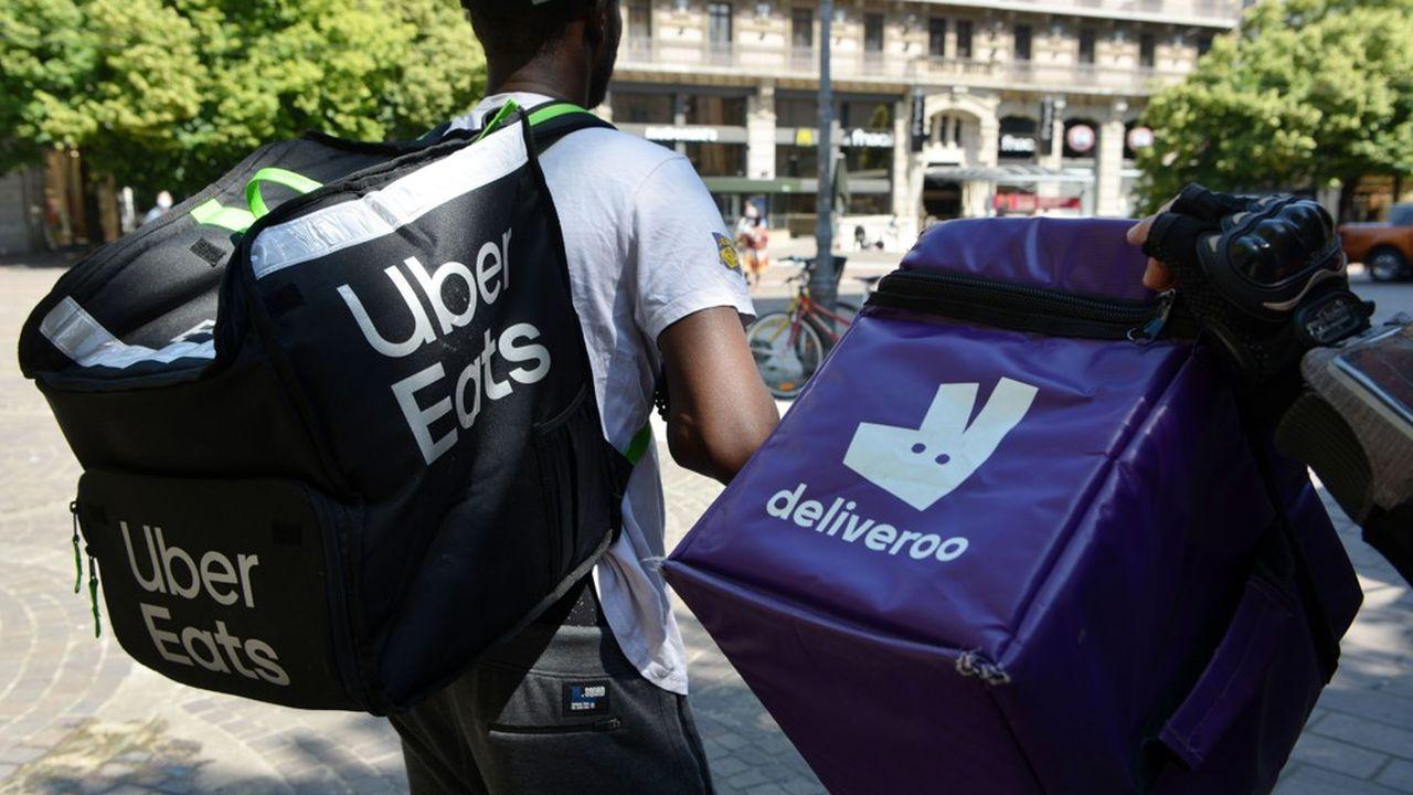 Deux livreurs d'Uber Eats et Deliveroo qui attendent des commandes pour la livraison.