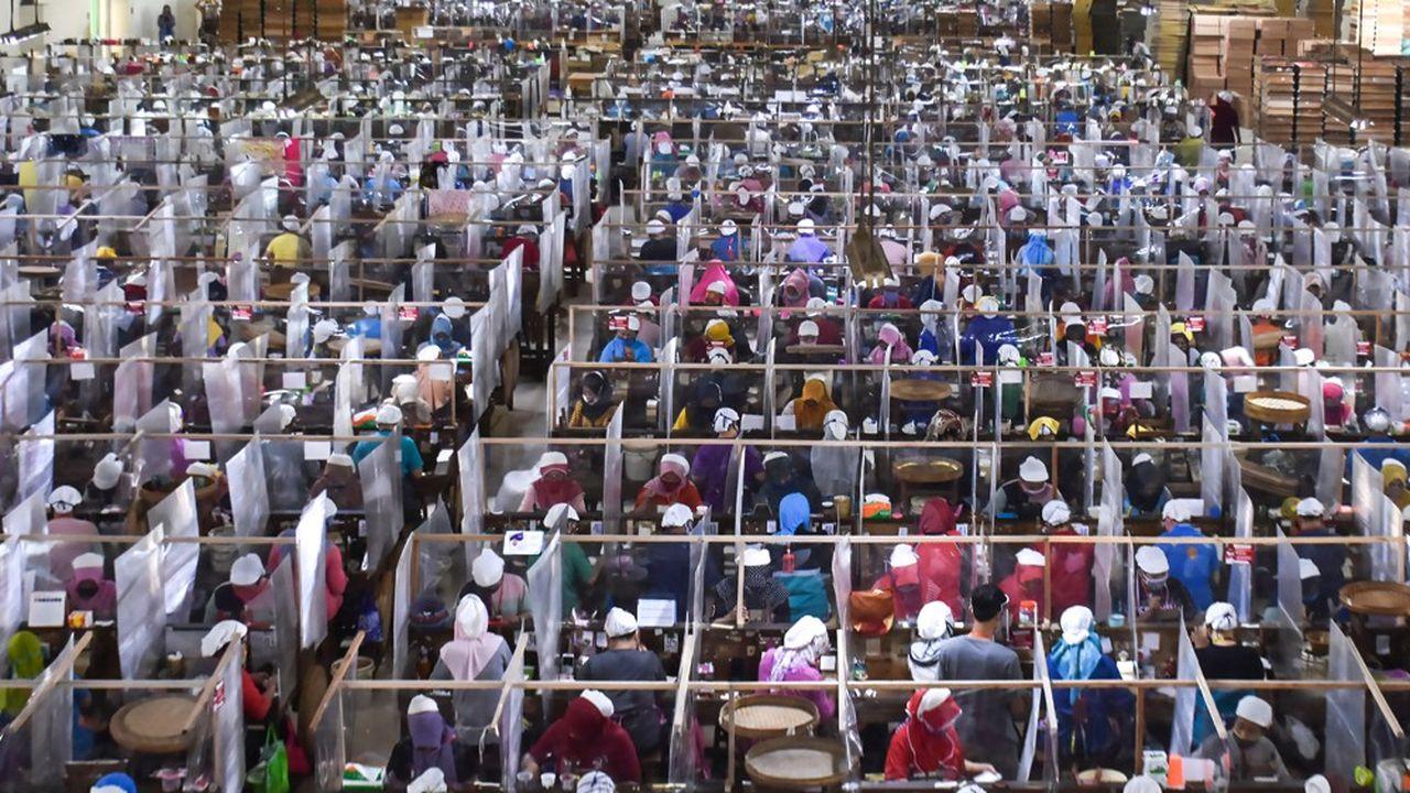 Des ouvriers roulent des cigarettes, protégés les uns des autres par des parois en plastique dans une usine indonésienne, à Java.