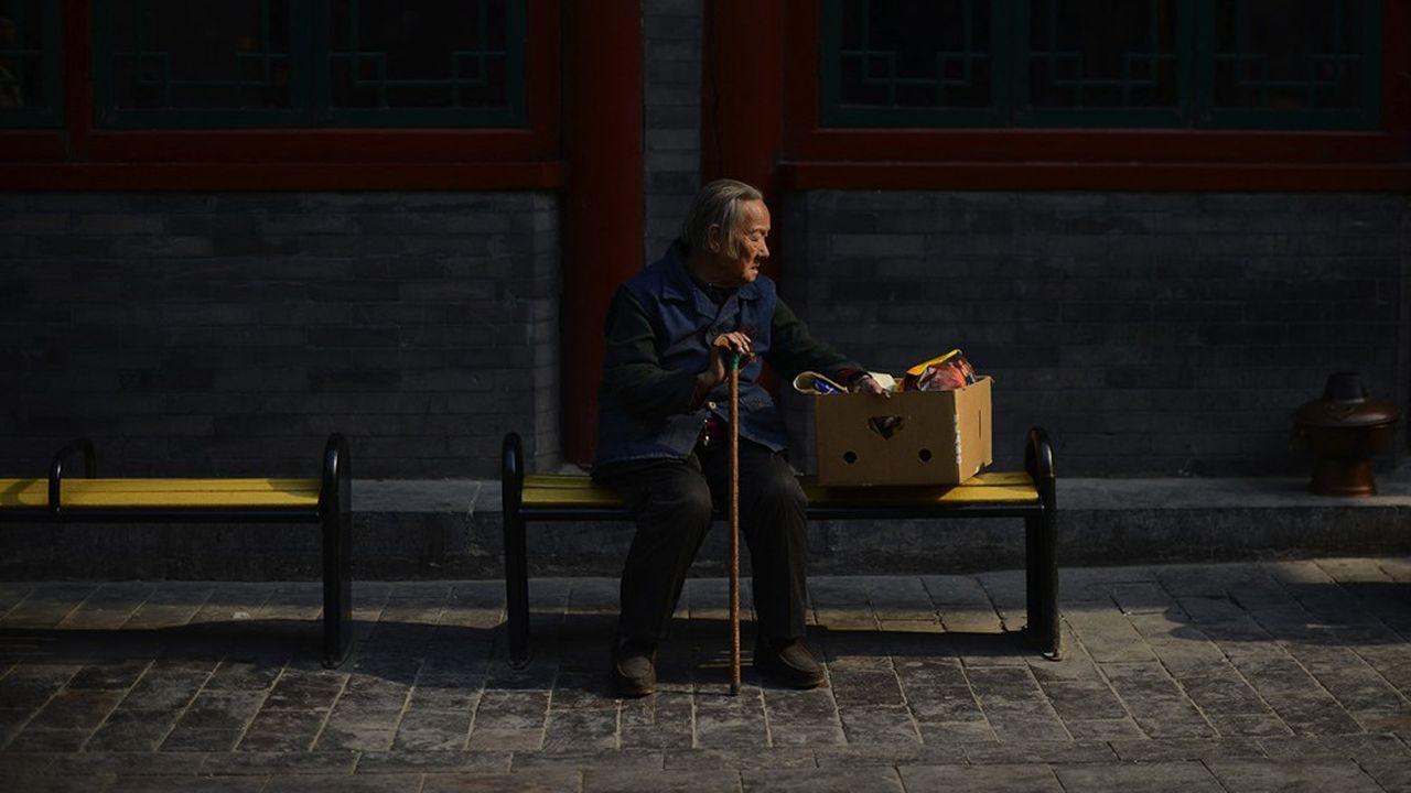 Une femme âgée sur un banc à Pékin.