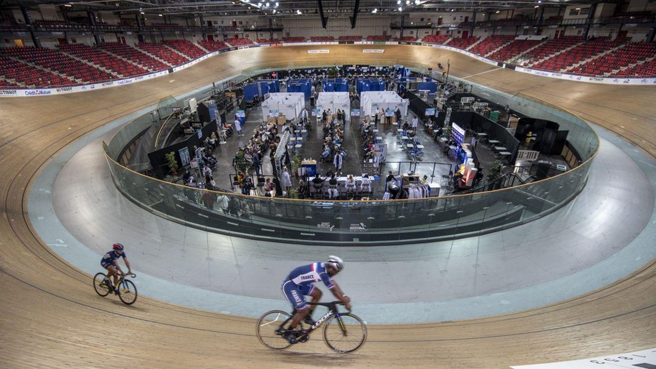 Des dizaines de personnes attendent d'être vaccinées, tandis que les champions cyclistes de l'équipe de France enchaînent les boucles sur piste