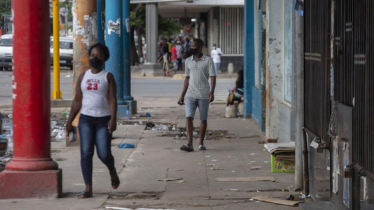 Des résidents de Maputo, au Mozambique, marchent masqués dans la ville.