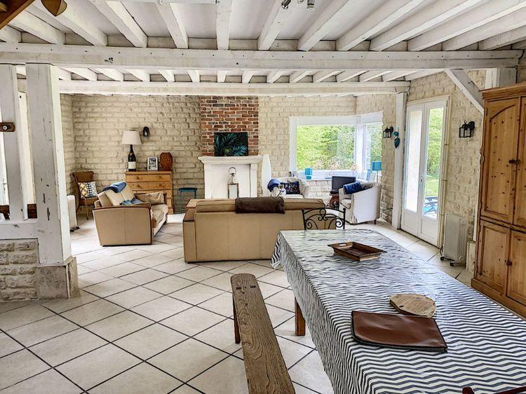 Au rez-de-chaussée, une grande pièce à vivre de 76 mètres carrés donne sur la terrasse et le jardin grâce à deux grandes portes-fenêtres.