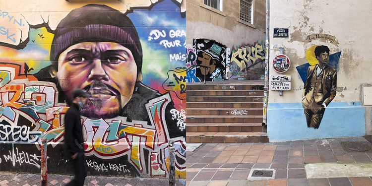A gauche, dans le quartier du cours Julien, le rappeur marseillais Le Rat Luciano par Pleks. Photo de droite, place de Lorette, Luiz « Mistral» Gustavo, ancien joueur de l'OM.