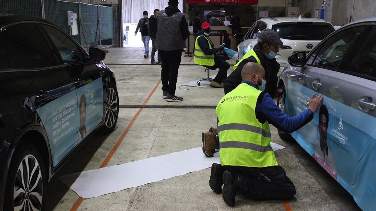 A Saint-Ouen et dans vingt métropoles, le chauffeur a à peine le temps de boire un café - offert - que sa voiture est nettoyée, le film posé, coupé et marouflé par quatre personnes qui s'activent autour du véhicule.